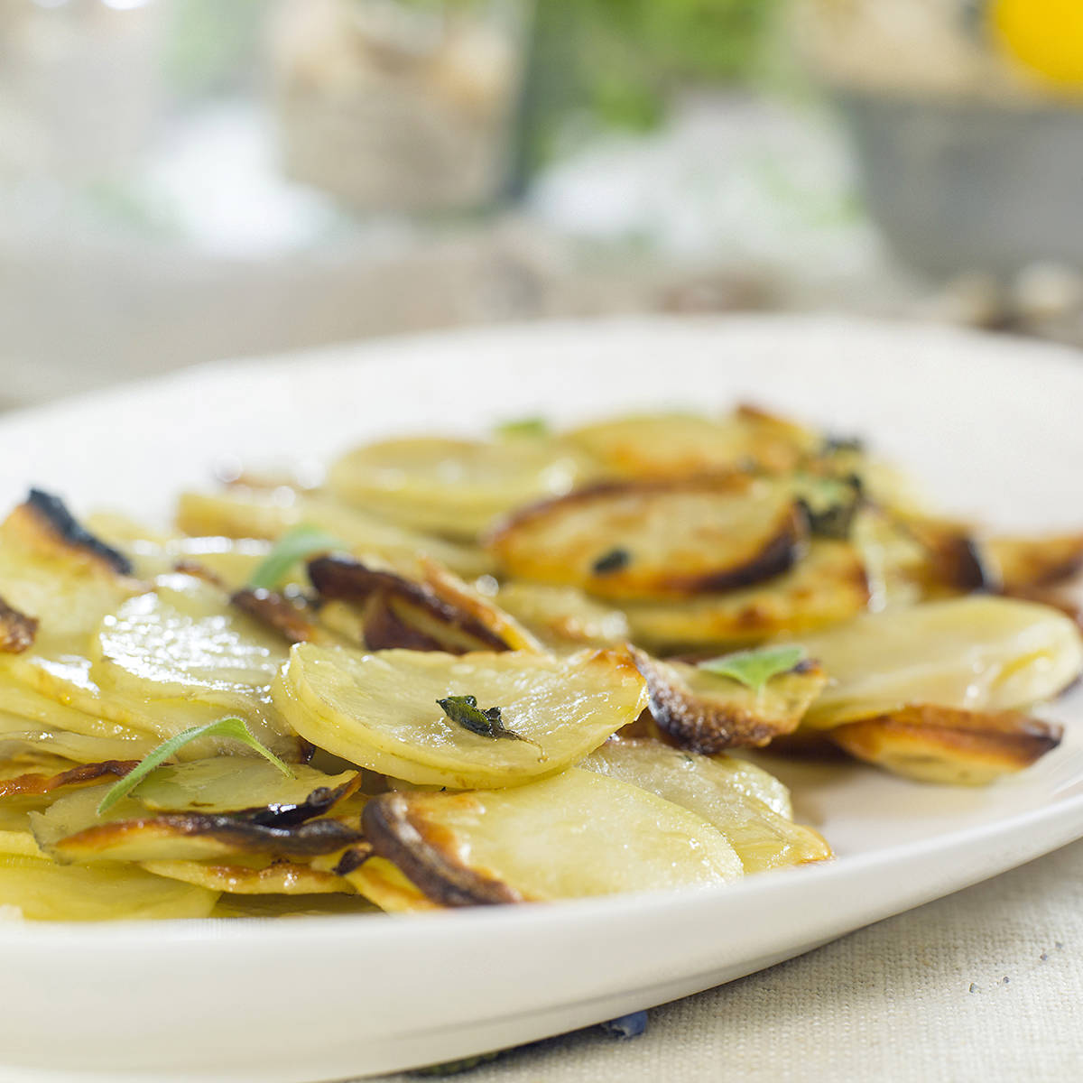 Urtefylt lammelår med ovnsbakte potetskiver og brun saus